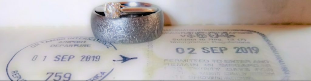 Wedding bands, one with a diamond and one with a finger print, placed on top of a passport