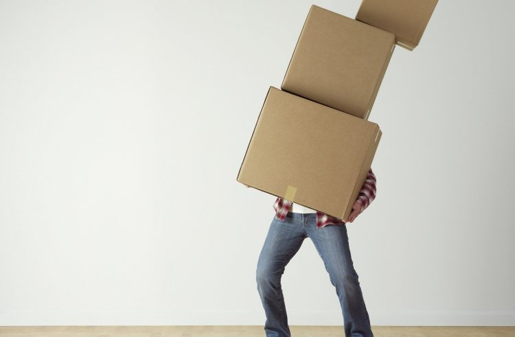 Adult male man with blue jeans, carrying 3 different size,brown moving boxes