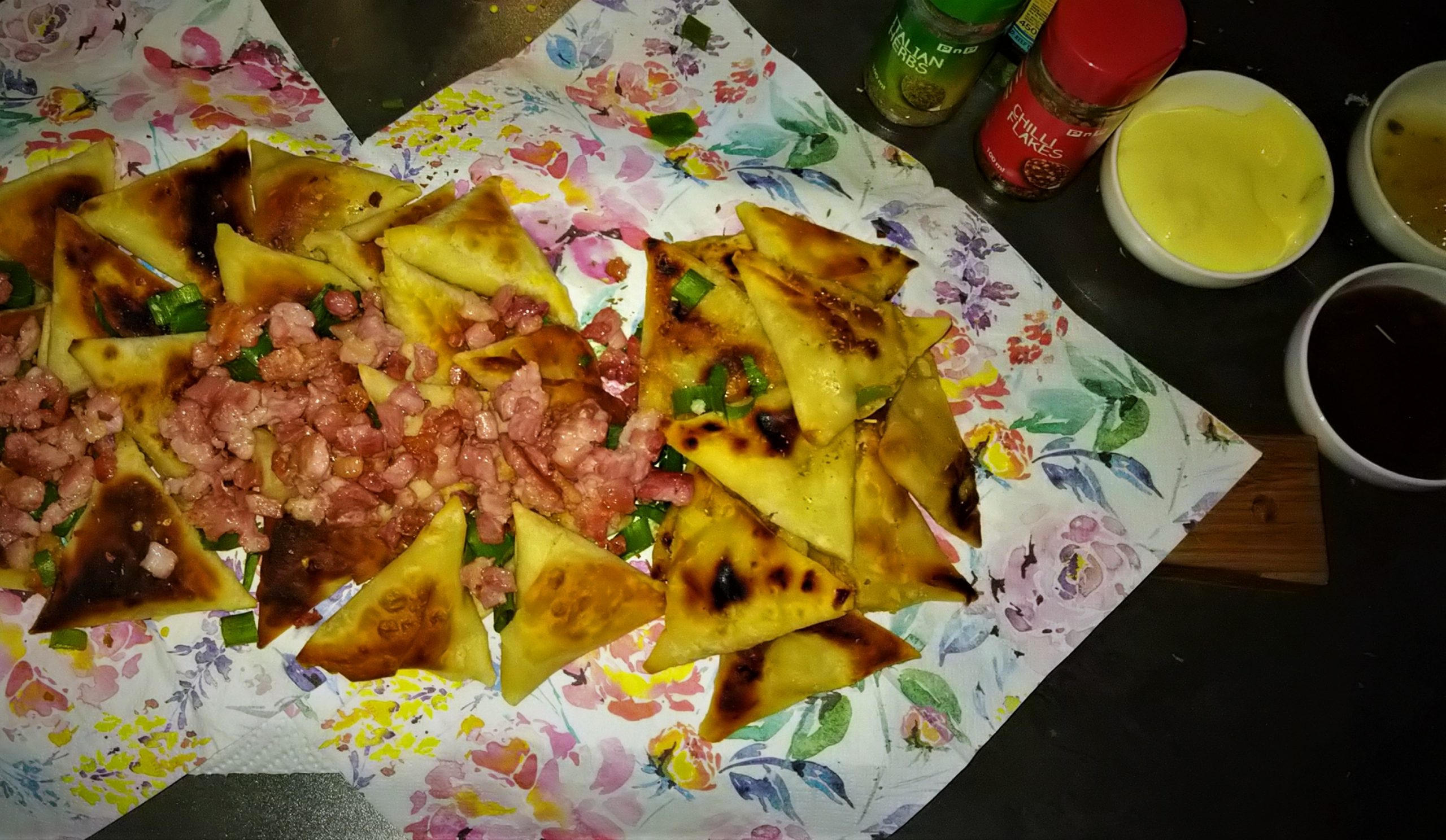 PnP Samoosa Beef, Chicken and Veggie served on a wooden platter and Floral Serviettes. Garnished with Spring Onion, Italian Herbs, Chilli Flakes and Bacon Bits. Served with Mayo, Chutney and Jalepino Sweet Chillie Sauce