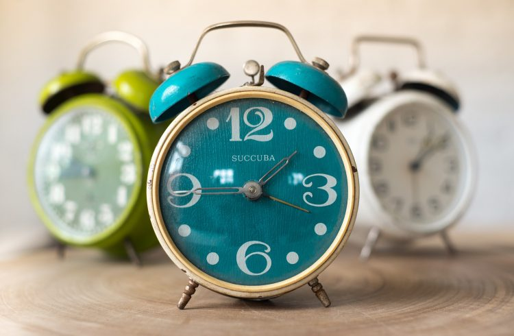 3 alarm clocks, turquoise, green and white on a wooden table
