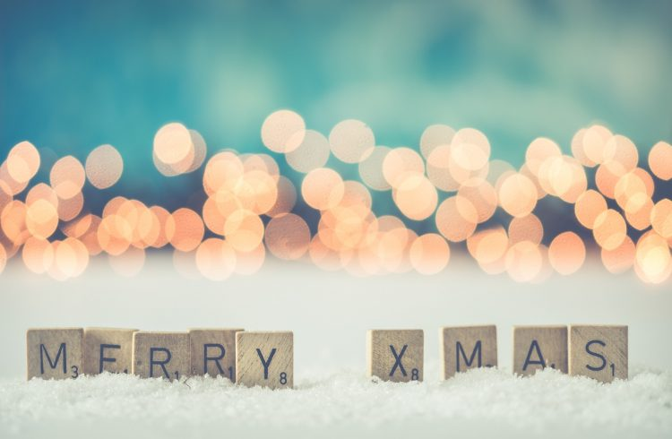 Wooden Blocks with Merry Christmas spelled out on them placed on a white fluffy carpet. The background has faded out warm white Christmas light with a turquoise hue behind the lights