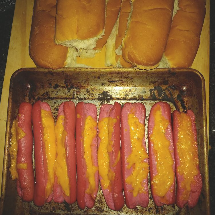 White and Buttered Hot Dog Buns and Cheesy Red Viennas on a baking tray on a wooden cutting board after Baking