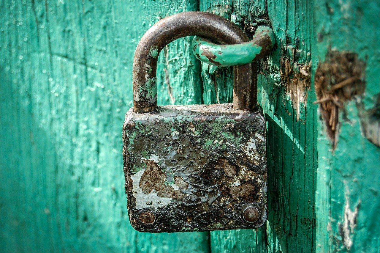 Rusty old padlock in a worn turquoise wooden door