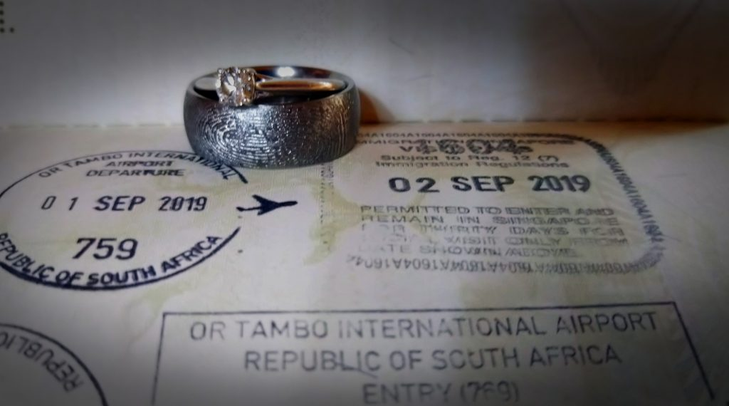 diamond-white-gold-ring-ontop-of-titanium-ring-with-fingerprint-engraving-stacked-ontop-of-south-african-passport-2-september-2019