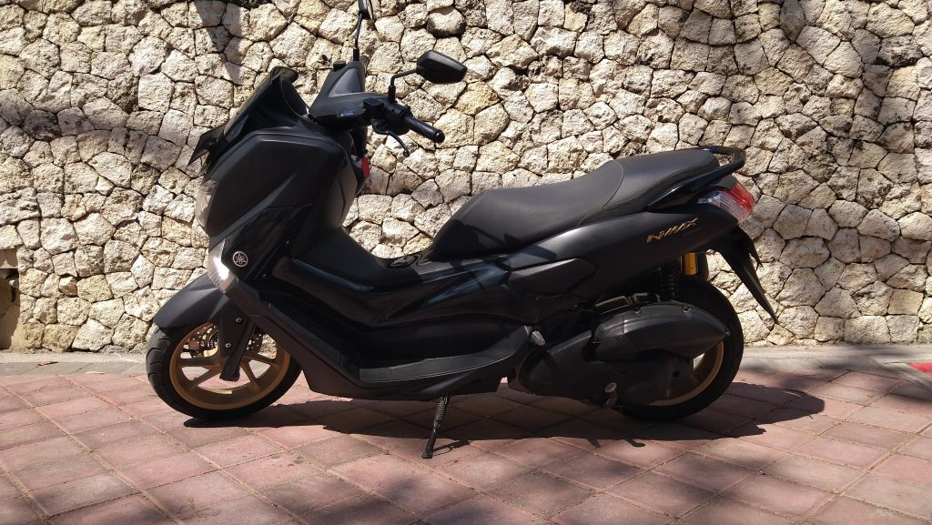 Black-and-gold-max-scooter-on-the-side-of-the-rode-by-sandstone-wall-in-Bali-Kuta