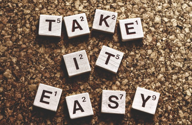 Take it Easy spelt out in white and black scrabble letters on a brown cork background