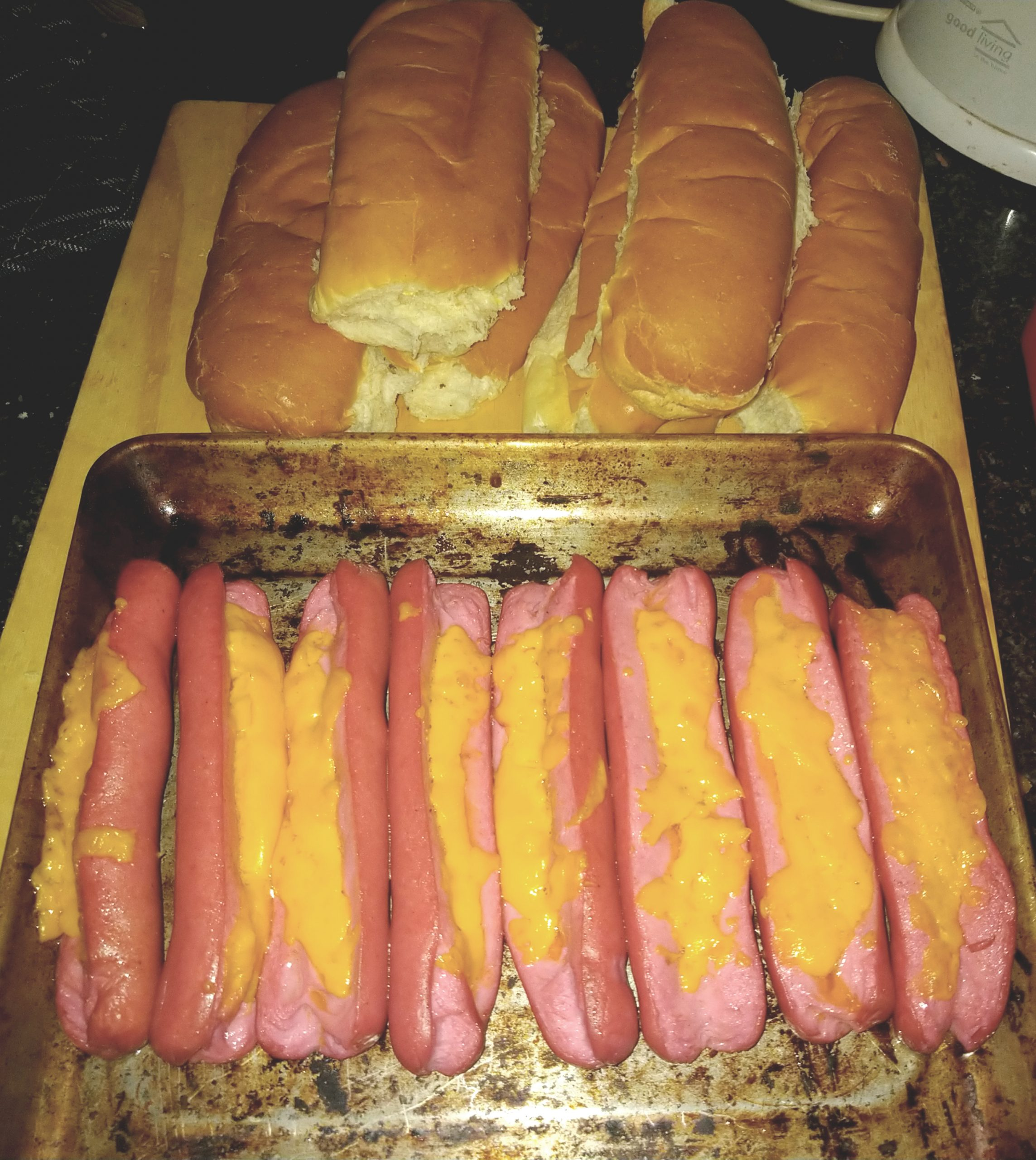 White and Buttered Hot Dog Buns and Cheesy Red Viennas on a baking tray on a wooden cutting board