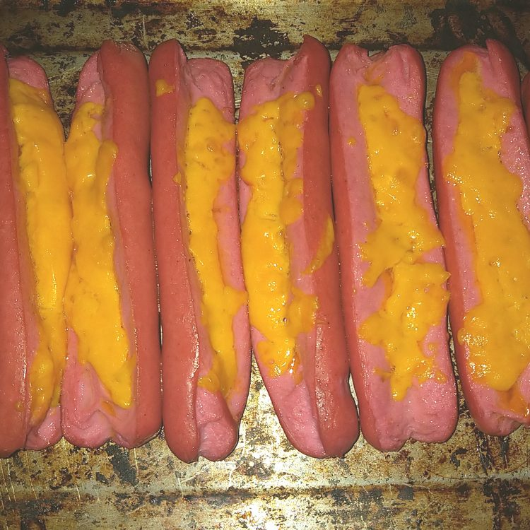 Sliced Red Viennas Stuffed with Cheddar Cheese on a Baking Tray After Baking
