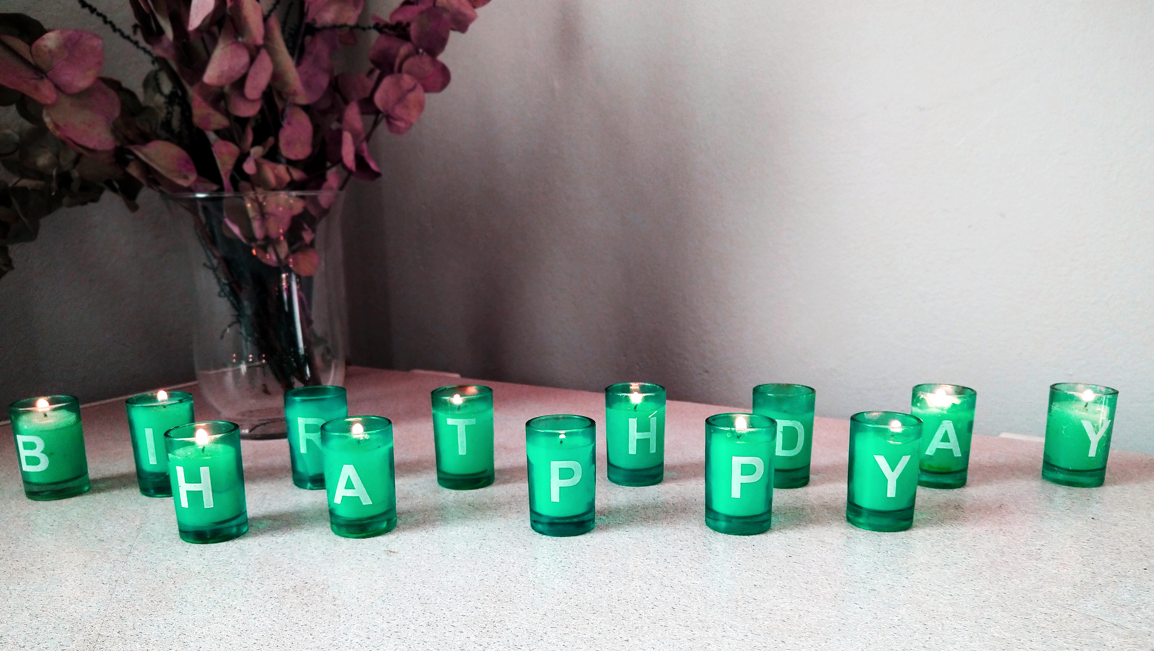 Happy Birthday spelled out with small blue candle holders with white candles inside that is lit.